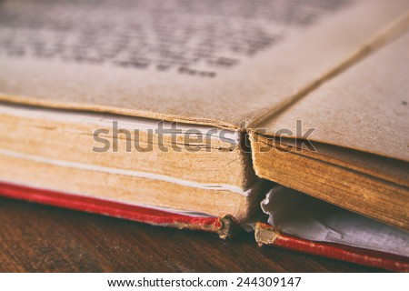 Open old book over wooden table. macro image with selective focus - stock photo