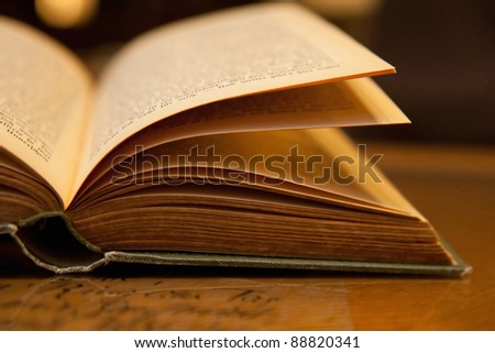 Open old book with warm light on a table - stock photo