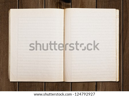 Open old notebook on a wooden table. - stock photo
