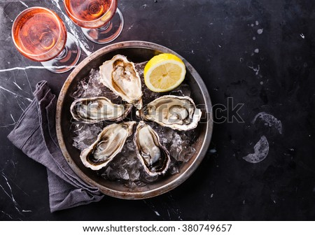 Open Oysters on metal plate and rose wine on dark marble background  - stock photo
