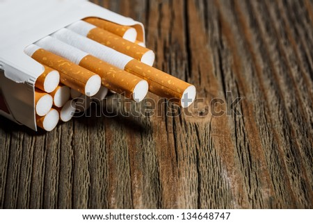 Open pack of cigarettes on old wooden table - stock photo