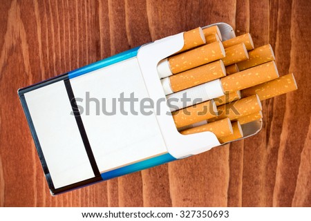 Open pack of cigarettes with the filter on brown table - stock photo