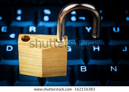 Open padlock on a glowing blue computer keyboard useful to illustrate data security - stock photo
