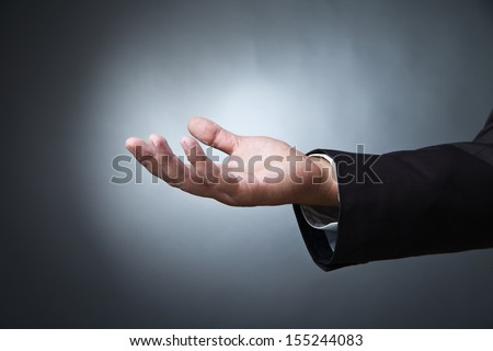 Open palm hand gesture of male hand on dark background - stock photo