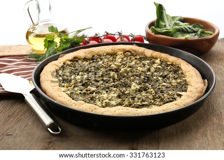 Open pie with spinach and tomato cherry on table close up - stock photo