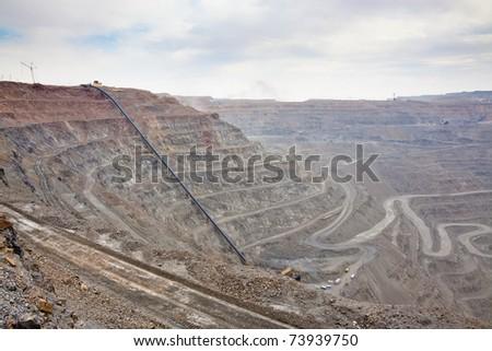 Open pit mine with ore conveyor - stock photo