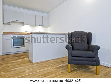 open plan kitchen view with armchair and wooden floor throughout - stock photo