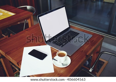 Open portable net-book and mobile phone with copy space screen for your text message or advertising content , laptop computer with cell telephone lying on a wooden table in cafe bar interior  - stock photo