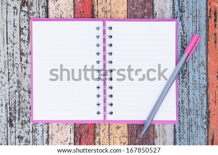 Open purple notebook and pen on vintage wood table for background and text  - stock photo