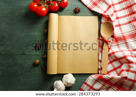 Open recipe book, vegetables and spices on wooden background - stock photo
