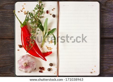 Open recipe book with chili and spices on a wooden background. - stock photo