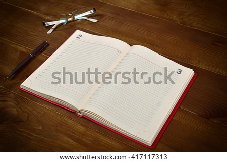open red leather diary, glasses and pen on wooden desk - stock photo