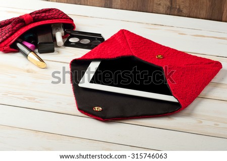 open red pen female handbag with tablet computer in a white wooden table. Near cosmetic bag with women's cosmetics. Mascara, eye shadow, lip gloss, nail polish - stock photo