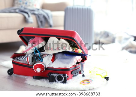 Open red suitcase on the floor, close up - stock photo