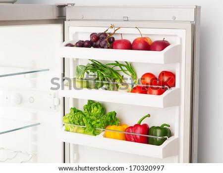 Open refrigerator full of fresh fruit and vegetables - stock photo