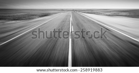 Open road ahead, endless road blur for concept in black and white - stock photo