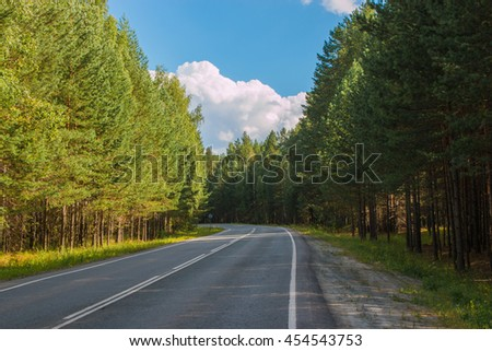 Open Road in future, no cars, auto on asphalt road through green forest, trees, pines, spruces. Clouds on blue sky in summer, sunshine, sunny day. Good weather. bokeh, blurred road - stock photo