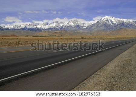 Open Road into the Snow Capped Mountains - stock photo