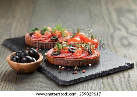 open rye sandwich with salami and vegetables - stock photo