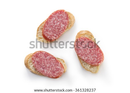 Open sandwiches canapes with salami salami on white background overhead - stock photo