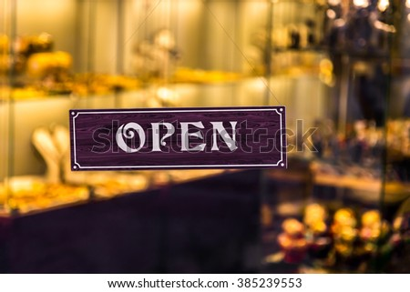 Open sign board close-up through the glass of a window at souvenir shop door. Shallow depth of field - stock photo