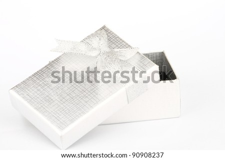 Open silver gift box with silver bowknot on white background - stock photo