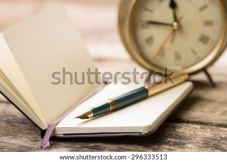 Open small notebook with fountain pen and old-fashioned alarm clock behind. Writing background image with selective focus - stock photo