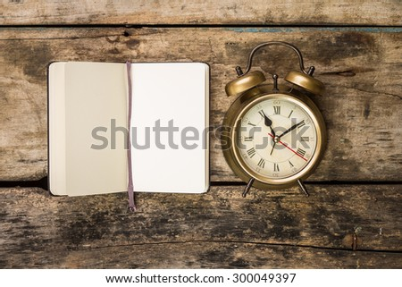 Open small notebook with retro-fashioned alarm clock . Top view writing vintage background - stock photo
