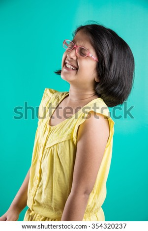 open smile of a small indian girl, asian girl laughing loudly, expressive small indian girl, indian small girl in glasses, indian girl wearing glasses - stock photo