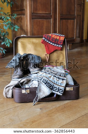 open suitcase full of warm clothes on the floor - stock photo
