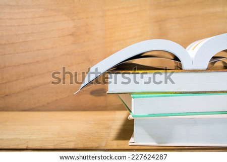 open Text books on wooden desk table and wooden background - stock photo