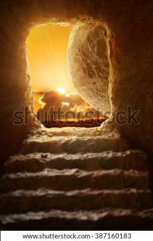 Open tomb of Jesus with sun appearing through entrance - Shallow depth of field on stone - stock photo
