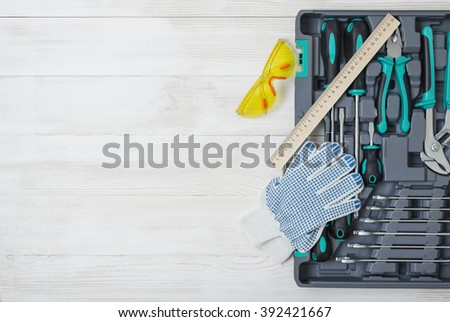 Open toolbox with different instruments on white wooden workbench. Clear space at center - stock photo