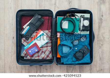 Open traveler's bag with clothing, accessories, credit card, tickets and passport, travel and vacations concept - stock photo