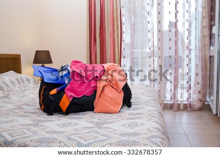 Open traveling bag with things in room on bed - stock photo