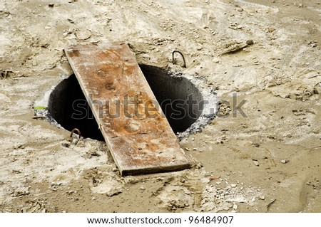 Open unsecured sewer manhole in the street - stock photo