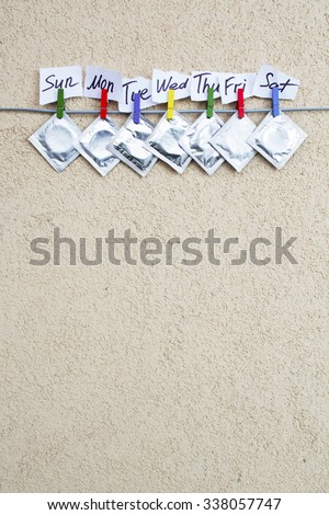 open (used) condom and sealed condoms on colorful clothespins. seven days of the week - sexweek, space for text.  - stock photo