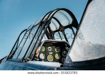 Open vintage airplane cockpit, blue sky background.  - stock photo