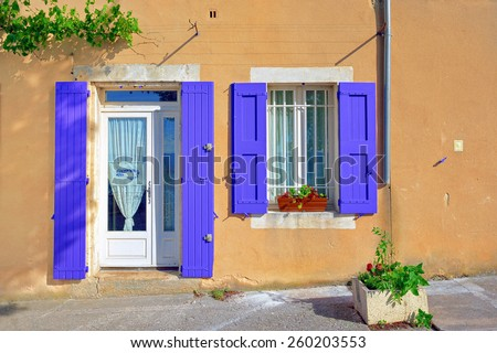 Open window and door with lavender color wooden shutters  on an ocher color plastered wall on a sunny day. Bonnieux village, Provence, France - stock photo