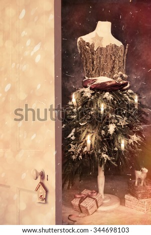 Open wooden door into Christmas with vintage mannequin with gifts - stock photo