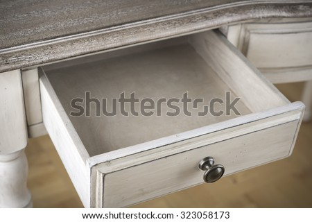 Open wooden drawer of vintage writing table - stock photo