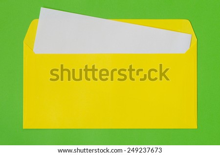 open yellow envelope with  blank paper on green background - stock photo