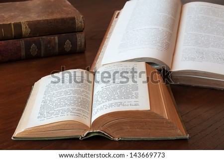 Opened and closed Rustic antique books on a wooden table - stock photo