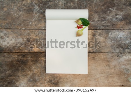 opened blank moleskine note books - soft pages texture - red flower and green leaf on old wood table background - stock photo