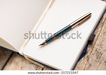 Opened blank notebook with elegant golden fountain pen on wooden background.  - stock photo