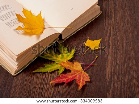 Opened book and autumn leaves on wooden table. Autumn mood concept - stock photo