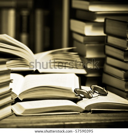 opened book, lying on the bookshelf with a glasses - stock photo