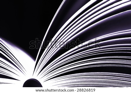 Opened book on dark background - purple version - stock photo