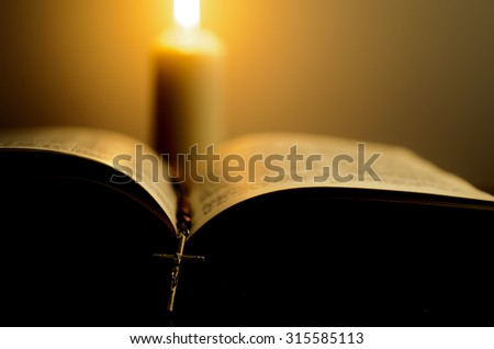 Opened book with rosary in front of the blurred burning candle. Shallow DOF. - stock photo