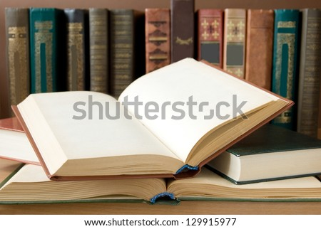 Opened books lying on the bookshelf - stock photo